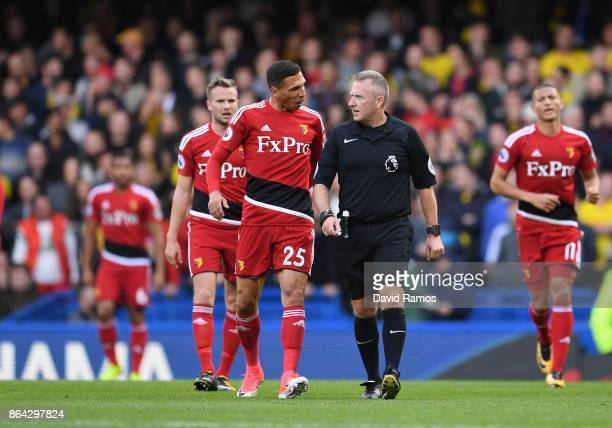 Jose Holebas of Watford in discussion with referee Jonathan Moss as Pedro of Chelsea scores the first goal during the Premier League match between...