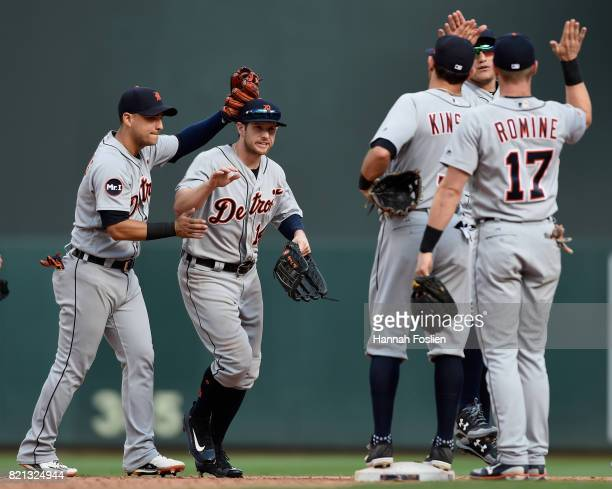 Jose Iglesias and Alex Presley of the Detroit Tigers celebrate winning against the Minnesota Twins with their teammates after the game on July 23...
