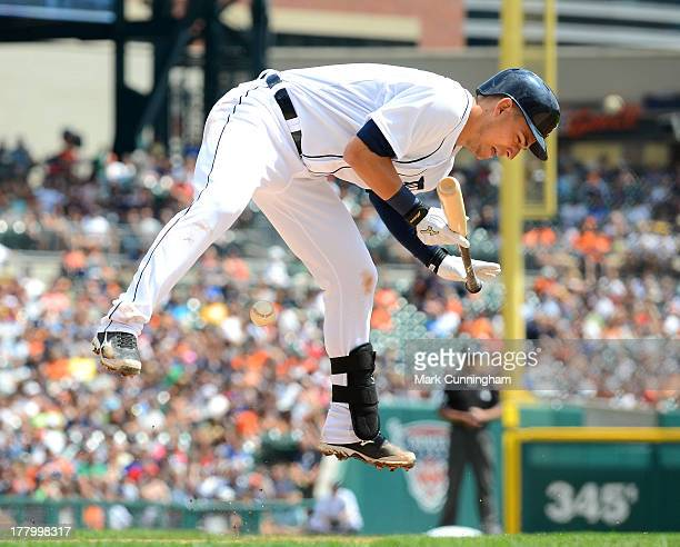 Jose Iglesias of the Detroit Tigers jumps into the air while getting hit by a pitch during game one of a doubleheader against the Kansas City Royals...