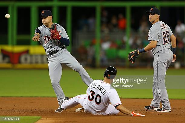 Jose Iglesias of the Detroit Tigers makes a throw to first as Placido Polanco of the Miami Marlins slides into second during a game at Marlins Park...