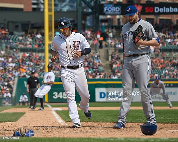 Jose Iglesias of the Detroit Tigers scores a run on a wild pitch by Steve Delabar of the Toronto Blue Jays during a MLB game at Comerica Park on July...