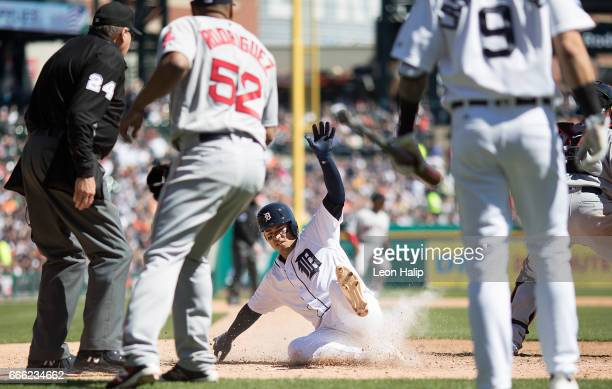 Jose Iglesias of the Detroit Tigers slides home on the single by Ian Kinsler during the fifth inning of the game against the Boston Red Sox on April...