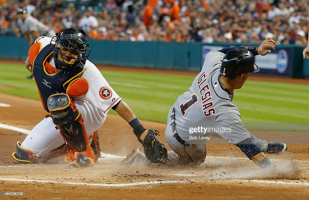 Jose Iglesias #1 of the Detroit Tigers slides past the tag of Hank Conger #16 of the Houston Astros in the first inning to score on a double by Miguel Cabrera #24 at Minute Maid Park on August 16, 2015 in Houston, Texas.