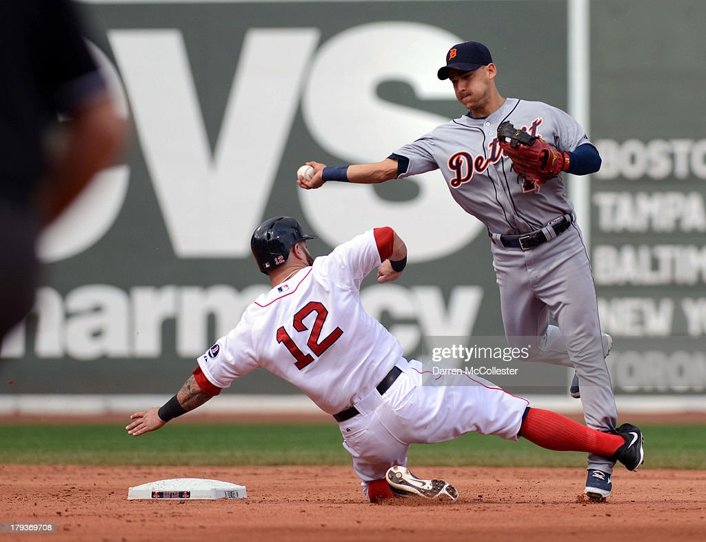 Jose Iglesias #1 of the Detroit Tigers turns the double play against a sliding <a gi-track='captionPersonalityLinkClicked' href=/galleries/search?phrase=Mike+Napoli&family=editorial&specificpeople=525007 ng-click='$event.stopPropagation()'>Mike Napoli</a> #12 of the Boston Red Sox in the second inning at Fenway Park on September 2, 2013 in Boston, Massachusetts.