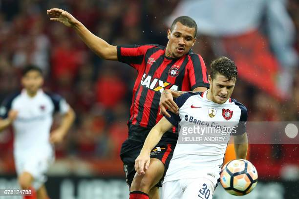 Jose Ivaldo of Atletico Paranaense struggles for the ball with Sabn Lorenzo's Bautista Merlini during their 2017 Libertadores Cup football match at...