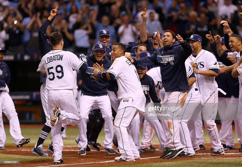 Jose Lobaton #59 of the Tampa Bay Rays is greeted at home by his teammates after hitting a walk off home run in the bottom of the ninth to defeat the Boston Red Sox during Game Three of the American League Division Series at Tropicana Field on October 7, 2013 in St Petersburg, Florida.