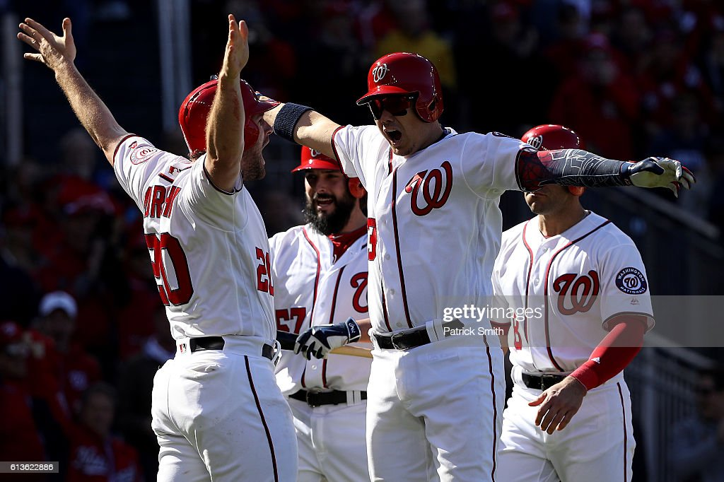 Jose Lobaton #59 of the Washington Nationals celebrates with teammates Danny Espinosa #8, Tanner Roark #57, and Daniel Murphy #20 after hitting a three run home run against the Los Angeles Dodgers in the fourth inning during game two of the National League Division Series at Nationals Park on October 9, 2016 in Washington, DC.