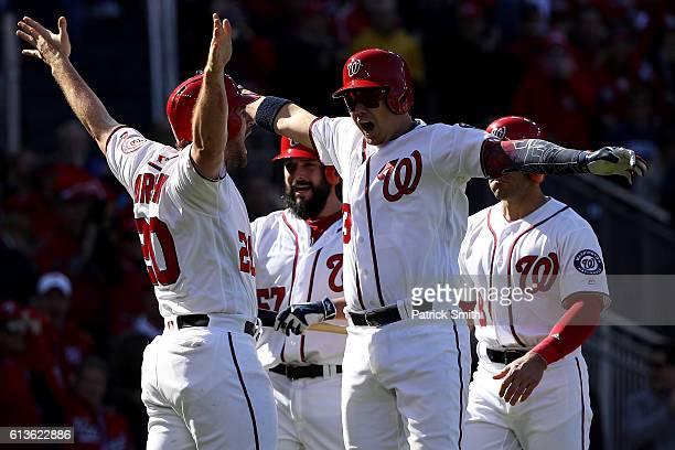 Jose Lobaton of the Washington Nationals celebrates with teammates Danny Espinosa Tanner Roark and Daniel Murphy after hitting a three run home run...