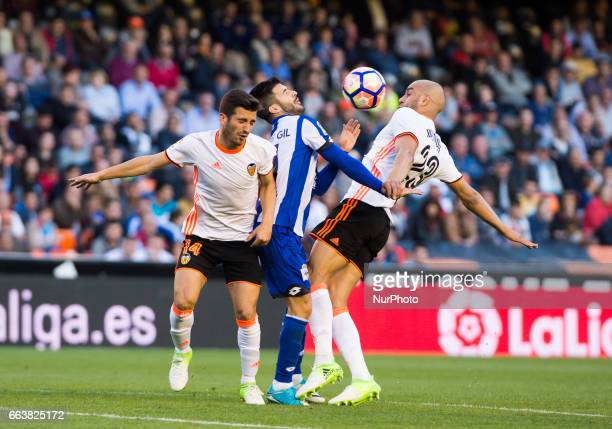 Jose Luis Gaya and Aymen Abdennour of Valencia CF and Carles Gil of Deportivo de la Corua during their La Liga match between Valencia CF and...