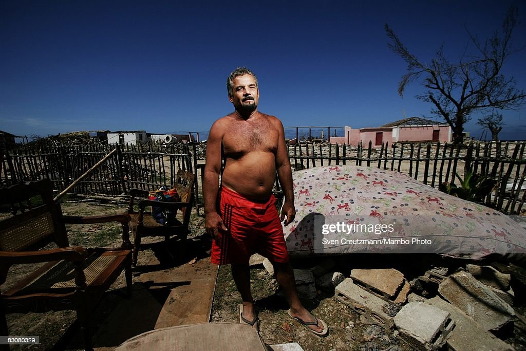Jose Luis Pena Morales stands in his garden where he has put a mattress out to dry against the backdrop of heavily damaged and destroyed houses after...