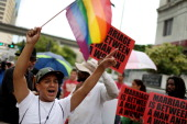 Jose Machado holds a rainbow flag near opponents of samesex marriage as people for and against gay marriage gather in front of the MiamiDade...