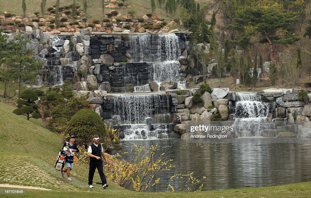 Jose Manuel Lara of Spain and his caddie walk past the waterfall on the fourth hole during the final round of the Ballantine's Championship at Blackstone Golf Club on April 28, 2013 in Icheon, South Korea.