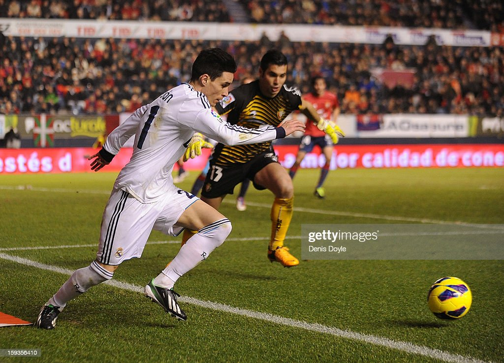 Jose Maria Callejon (L) of of Real Madrid battles for the ball with Andres Fernandez of Osasuna during the La Liga match between Osasuna and Real Madrid at estadio Reino de Navarra on January 12, 2013 in Pamplona, Spain.