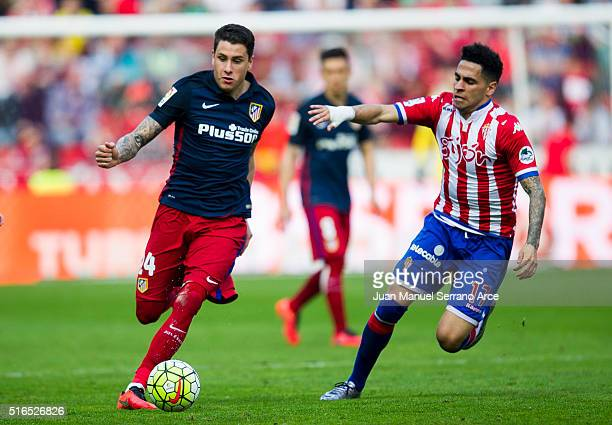 Jose Maria Gimenez of Club Atletico de Madrid duels for the ball with Mascarell of Real Sporting de Gijon during the La Liga match between Real...