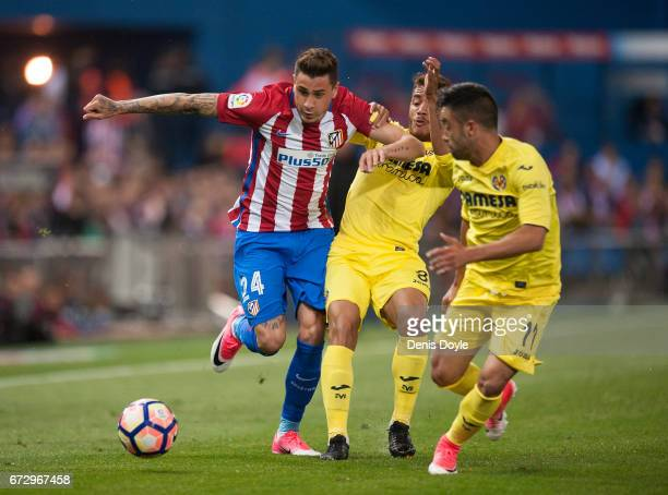 Jose Maria Gimenez of Club Atletico de Madrid is challenged by Jonathan Dos Santos of Villareal CF during the La Liga match between Club Atletico de...