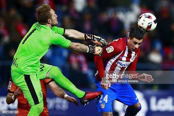 Jose Maria Gimenez wins the header before goalkeeper Yoel Rodriguez of SD Eibar during the Copa del Rey quarterfinal match between Club Atletico de...