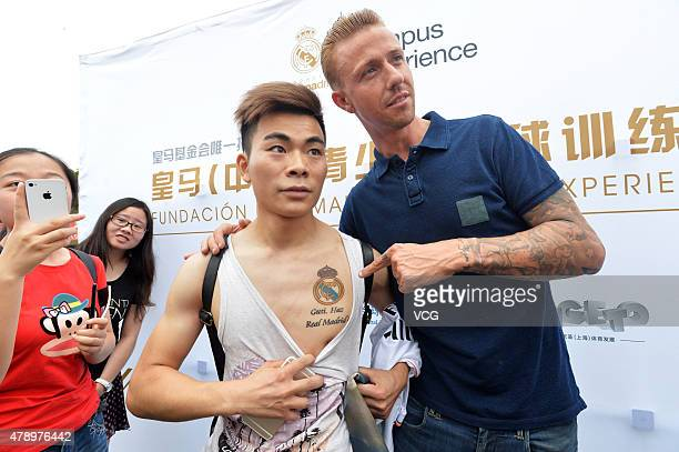 Jose Maria Gutierrez 'Guti'poses with a fan who has a tattoo of Guti's name on his chest as Real Madrid's Campus Experience opens on June 29 2015 in...