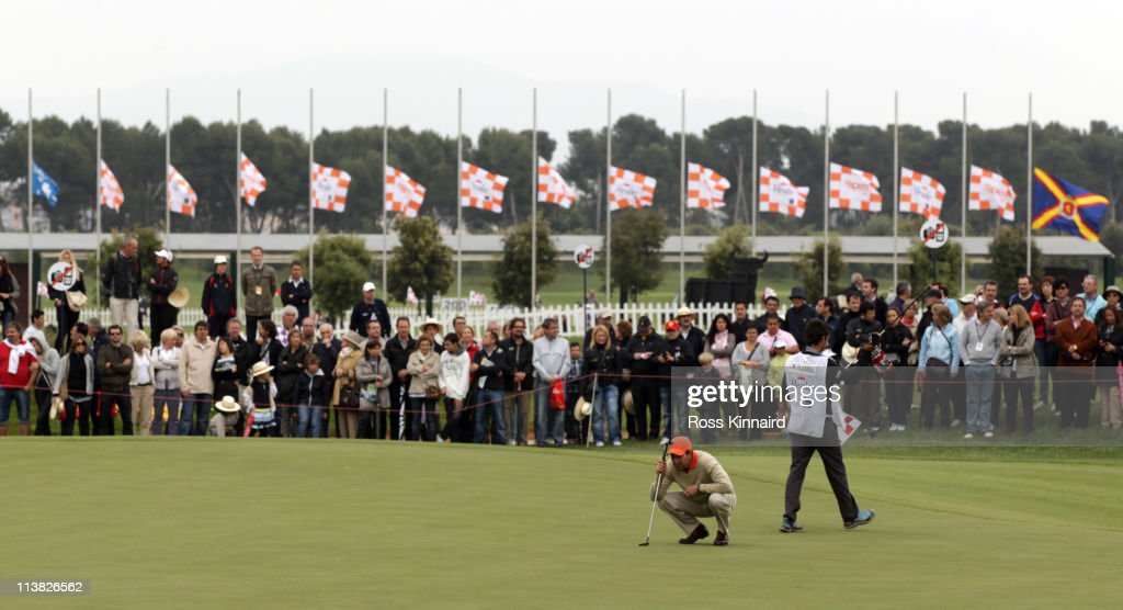 Jose Maria Olazabal of Spain putting on the 18th green with the flags flying at half mast following news of the death of Seve Ballesteros during the...