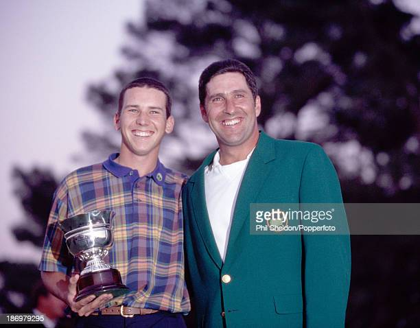 Jose Maria Olazabal of Spain wearing the green jacket next to golfer Sergio Garcia who is holding the trophy for lowest amateur score after winning...