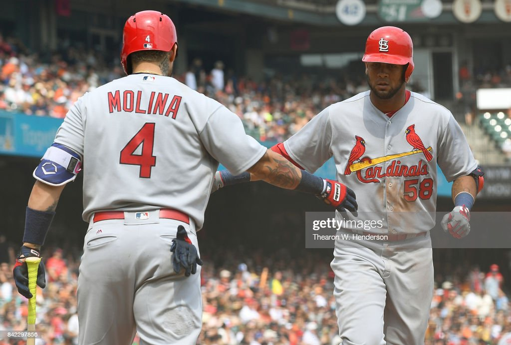 Jose Martinez #58 of the St. Louis Cardinals congratulated by Yadier Molina #4 after Martinez hit a solo home against the San Francisco Giants in the top of the fourth inning at AT&T Park on September 3, 2017 in San Francisco, California.