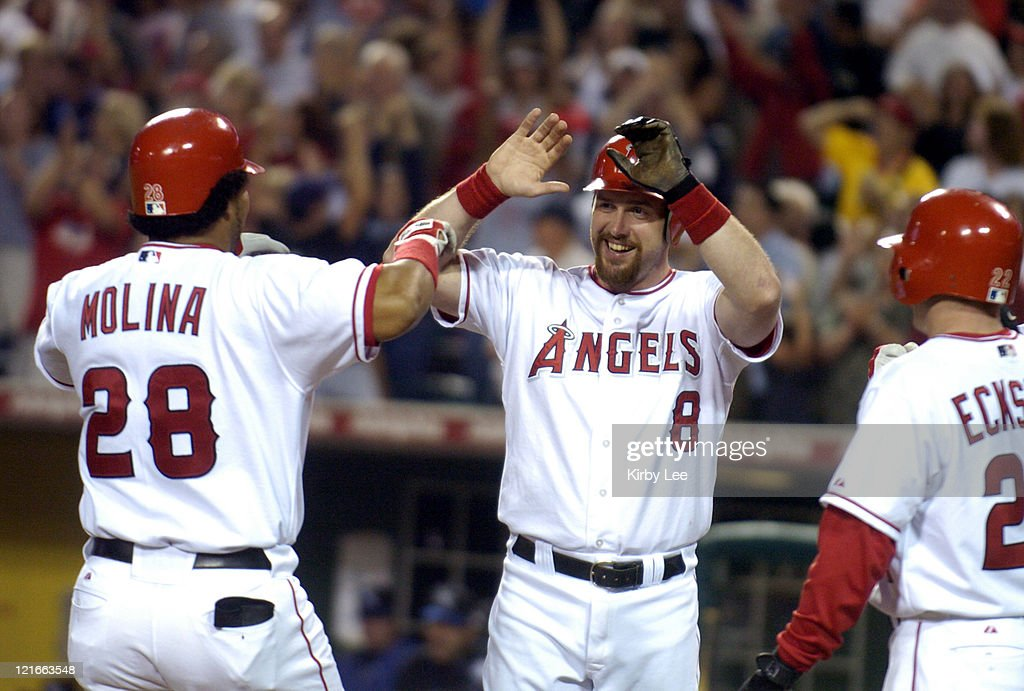 Jose Molina (28) of the Anaheim Angels is greeted by Josh Paul (8) and David Eckstein (22) after hitting a seventh-inning grand slam in 21-6 victory over the Kansas City Royals at Angel Stadium in Anaheim, Calif. on Wednesday, August 25, 2004. Anaheim's 21 runs were the most for a home game in club history.