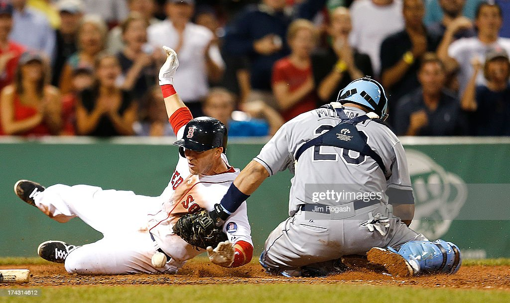 Jose Molina #28 of the Tampa Bay Rays drops the ball as Stephen Drew #7 of the Boston Red Sox scores in the 8th inning at Fenway Park on July 23, 2013 in Boston, Massachusetts.