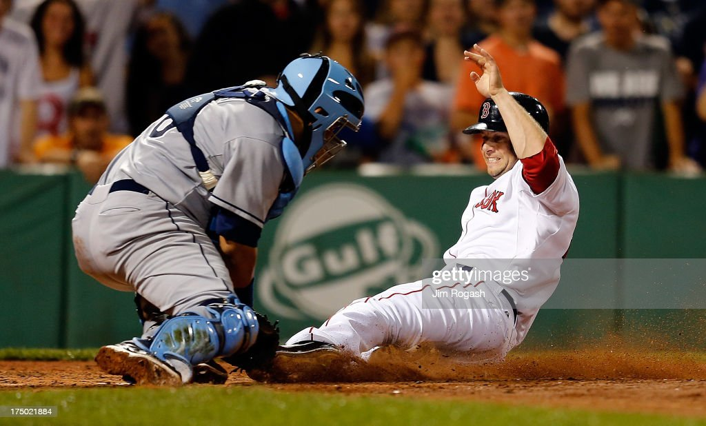 Jose Molina #28 of the Tampa Bay Rays tags out base runner Daniel Nava #29 of the Boston Red Sox in the 8th inning at Fenway Park on July 29, 2013 in Boston, Massachusetts.