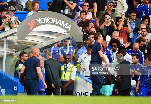 Jose Mourinho Manager of Chelsea celebrates his team's 20 win with his players while Arsene Wenger Manager of Arsenal leaves the pitch after the...