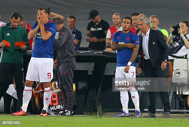 Jose Mourinho Manager of Manchester United talks to Memphis Depay of Manchester United as he and Zlatan Ibrahimovic of Manchester United covers his...
