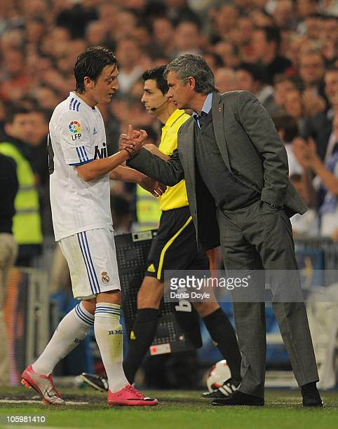Jose Mourinho manager of Real Madrid shakes hands with Mesut Ozi of Real after he was substituted during the La Liga match between Real Madrid and...