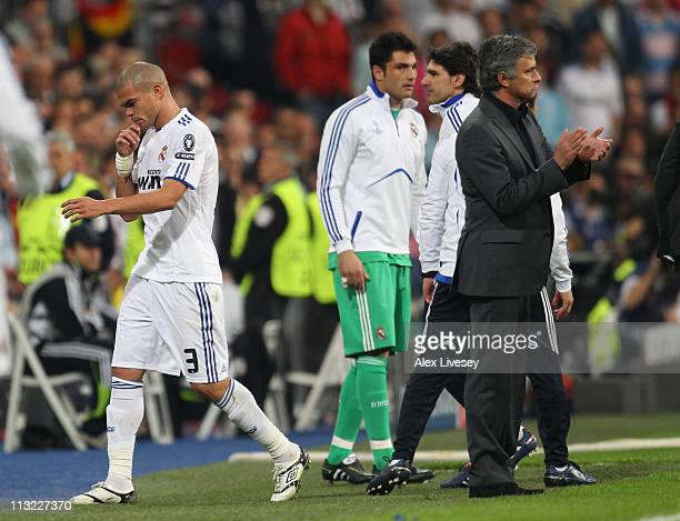 Jose Mourinho the coach of Real Madrid applauds the referee as Pepe is sent off during the UEFA Champions League Semi Final first leg match between...