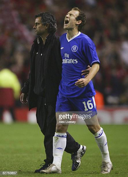 Jose Mourinho the manager of Chelsea and Arjen Robben walk off the pitch dejected after being defeated by Liverpool in the Champions League semi...