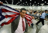 Jose Nunez born in Mexico celebrates holding up the US flag after taking the oath of citizenship at a naturalization ceremony at the Los Angeles...