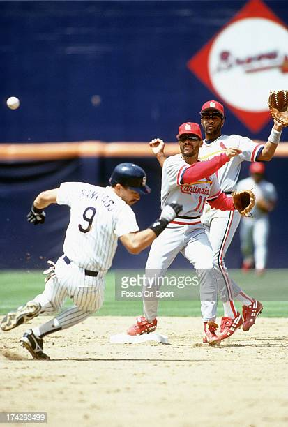 Jose Oquendo of the St Louis Cardinals gets his throw off to first base with Benito Santiago of the San Diego Padres sliding in at second base during...