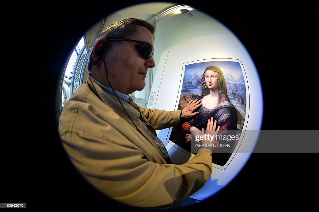 Jose Pedro Gonzalez a 56yearold blind visitor touches a painting using a relief painting technique that adds volume and texture a copy of 'Mona Lisa'...