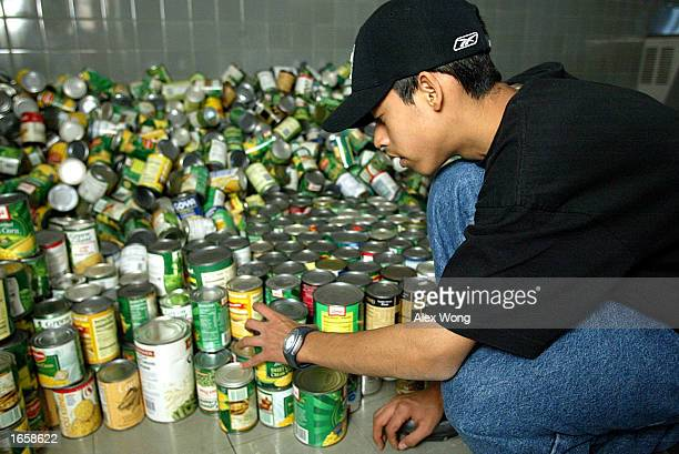 Jose Pena helps sort food collected for Archbishop Carroll High School's annual food drive program November 24 2002 in Washington DC Students faculty...
