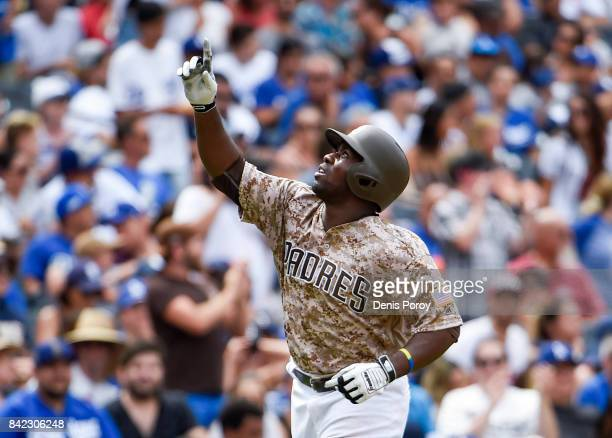 Jose Pirela of the San Diego Padres points skyward after hitting a solo home run during the fifth inning of a baseball game against the Los Angeles...