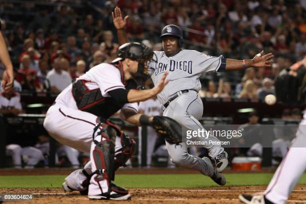 Jose Pirela of the San Diego Padres safely slides into home plate to score a run past catcher Jeff Mathis of the Arizona Diamondbacks during the...