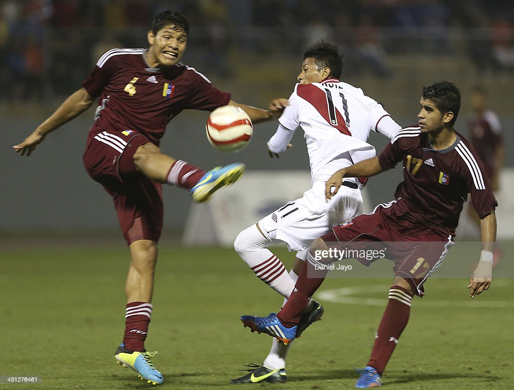Jose Po (L) and Francisco Diaz of Venezuela compete for the ball with (R) Kevin Ruiz, of Peru during a U18 match between Peru and Venezuela as part of the XVII Bolivarian Games Trujillo 2013 at Mansiche Stadium on November 21, 2013 in Lima, Peru.