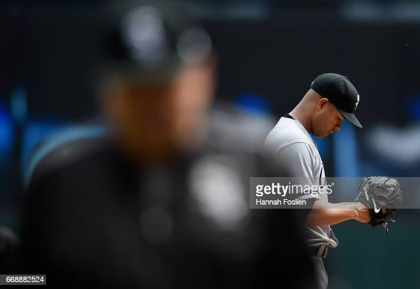 Jose Quintana of the Chicago White Sox looks on as pitching coach Don Cooper returns to the dugout after a visit to the mound during the first inning...