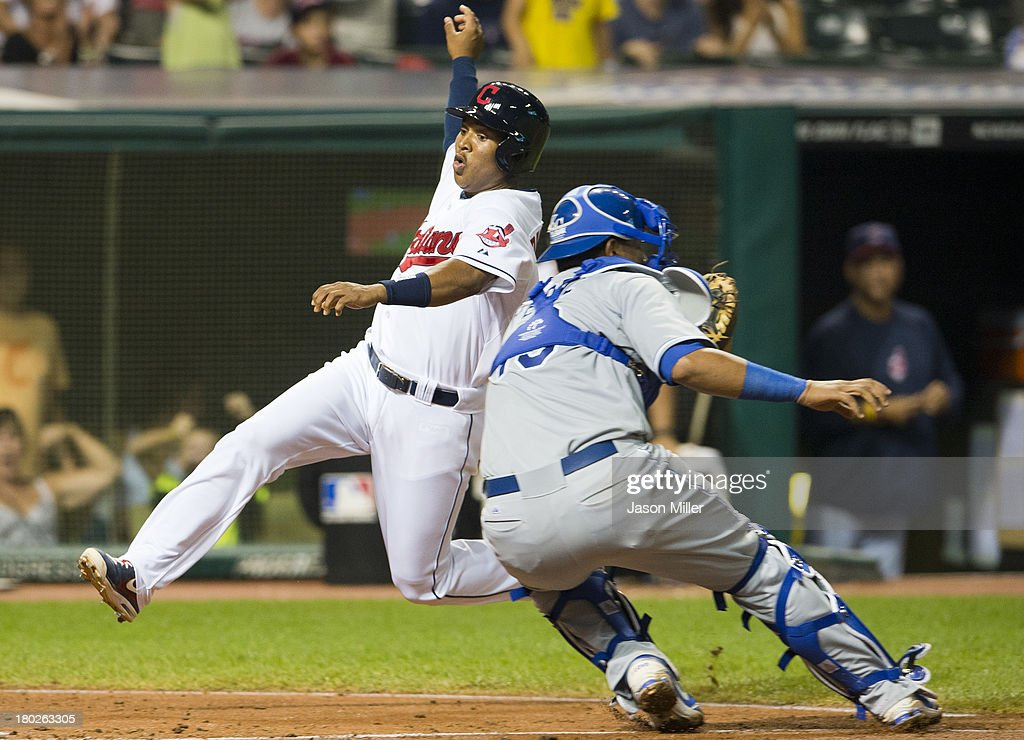 Jose Ramirez #62 of the Cleveland Indians dives past catcher Salvador Perez #13 of the Kansas City Royals to score off a double by Michael Bourn #24 during the seventh inning at Progressive Field on September 10, 2013 in Cleveland, Ohio.