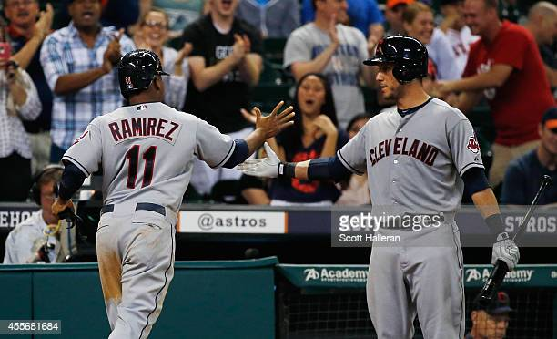 Jose Ramirez of the Cleveland Indians is greeted by teammate Mike Aviles after Ramirez scored a run against the Houston Astros in the ninth inning...