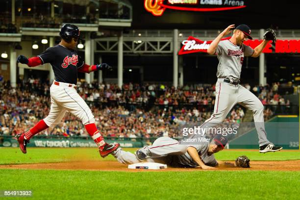 Jose Ramirez of the Cleveland Indians is out at first as first baseman Joe Mauer makes the tag under pitcher Michael Tonkin of the Minnesota Twins at...
