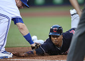 Jose Ramirez of the Cleveland Indians is picked off first base in the sixth inning during MLB game action as Justin Smoak of the Toronto Blue Jays...
