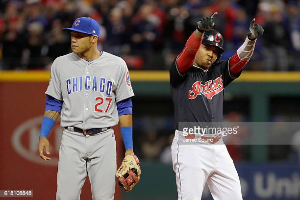 Jose Ramirez of the Cleveland Indians reacts after hitting a double during the sixth inning as Addison Russell of the Chicago Cubs looks on in Game...