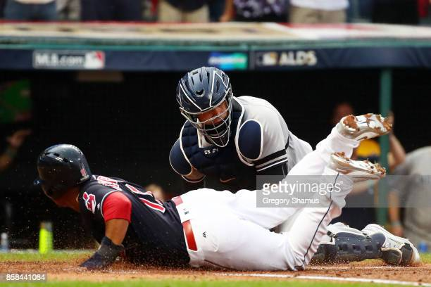 Jose Ramirez of the Cleveland Indians slides into home to score on a hit by Carlos Santana against Gary Sanchez of the New York Yankees in the first...
