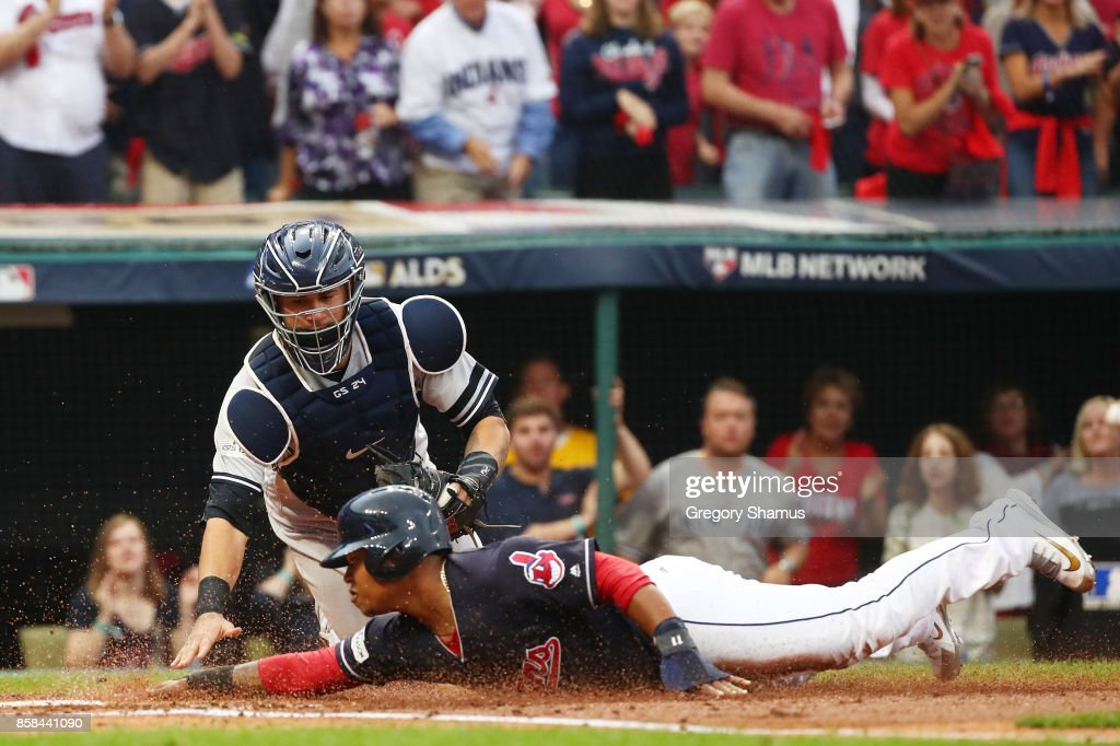 Jose Ramirez #11 of the Cleveland Indians slides into home to score on a hit by Carlos Santana #41 against Gary Sanchez #24 of the New York Yankees in the first inning during game two of the American League Division Series at Progressive Field on October 6, 2017 in Cleveland, Ohio.
