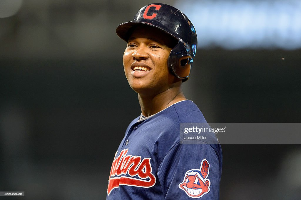 Jose Ramirez #11 of the Cleveland Indians talks with players in the visitors dugout while standing on first during the seventh inning against the Minnesota Twins at Progressive Field on September 9, 2014 in Cleveland, Ohio.