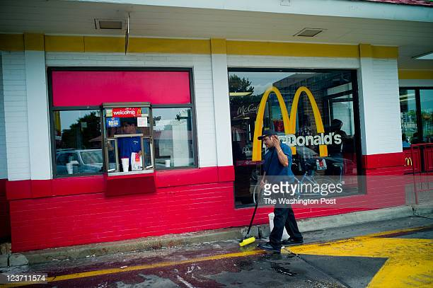 Jose Reyes mops the drive thru while Marvin Mateo gets an order ready at the drivethru window Capitol Hill SE McDonald's