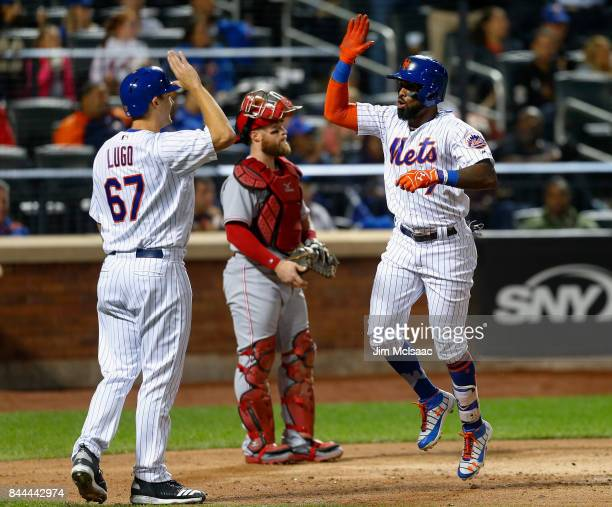 Jose Reyes of the New York Mets celebrates his fifth inning two run home run with teammate Seth Lugo as Tucker Barnhart of the Cincinnati Reds looks...